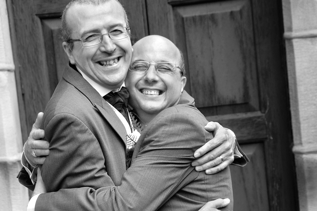 Groom and bestman hugging and laughing, wedding photography at Catholic church, Derbyt